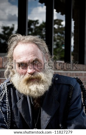 Homeless man with blue eyes and white beard. - stock photo