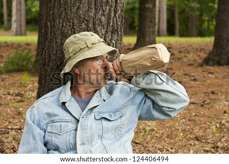 homeless man with his bottle in a park - stock photo