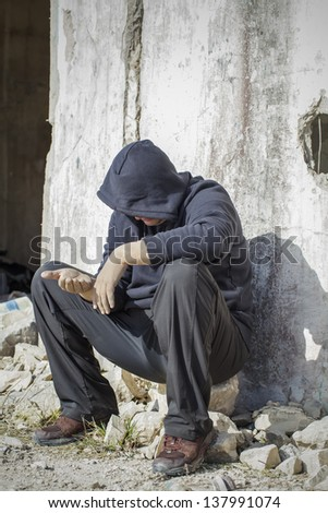 Homeless person begging near the old house