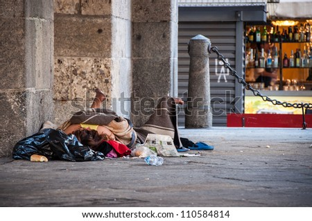 Homeless person sleeping on the street in Milan, Italy - stock photo