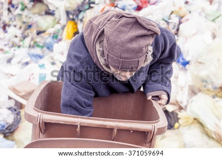 homeless rummages in the dustbin of landfill - stock photo