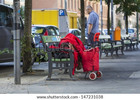 Homeless sleeping on a bench in the street - stock photo