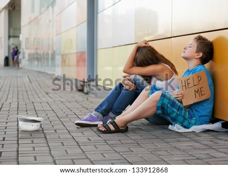 Homeless teenage boy and girl begging in street (The production scene; problem-free children play a role of beggars) - stock photo