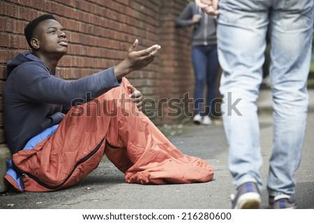 Homeless Teenage Boy Begging For Money On The Street - stock photo