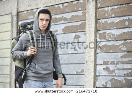 Homeless Teenage Boy On Street With Rucksack - stock photo