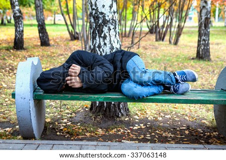 Homeless Teenager sleep on the Bench in the Autumn Park - stock photo