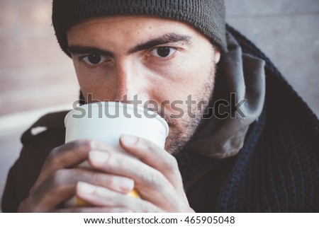 Homeless whit dirty hands drinking alone