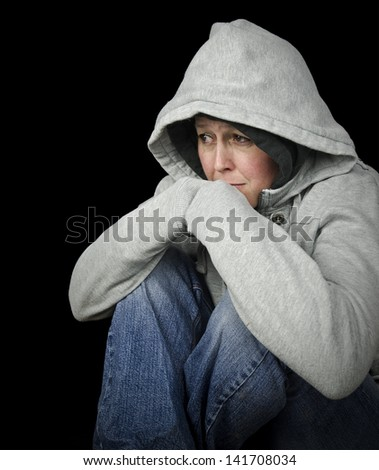 homeless woman sitting on floor, black background with copy space - stock photo