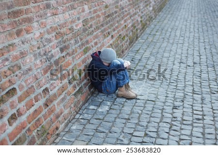 homeless young boy leaned against the wall - stock photo