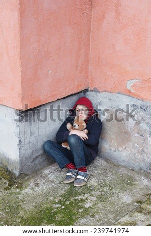 homeless young boy leaned against the wall with bear - stock photo