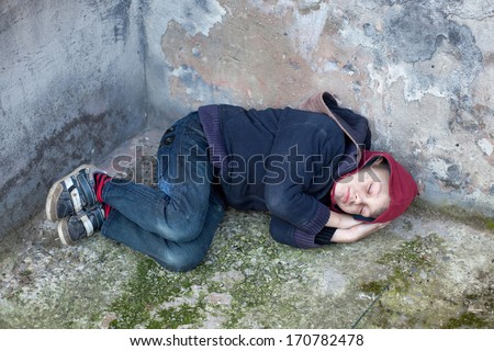 homeless young boy sleeps under the wall  - stock photo