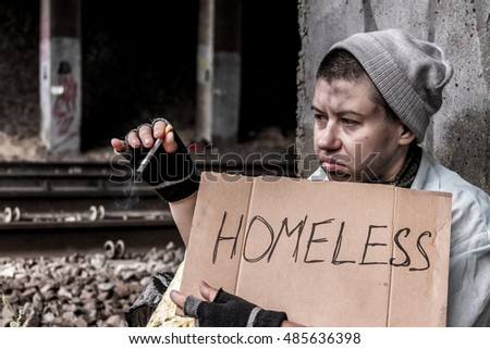 Homeless young woman with sign sitting near the rail track and smoking