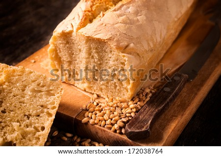 Homemade and baked white bread on the wooden board.Selective focus in the middle  - stock photo