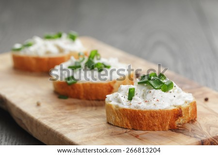 homemade appetizing crostini with soft cheefe cream and onion chives