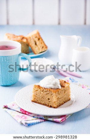 Homemade apple cake, slice with cream on plate, served for tea, selective focus