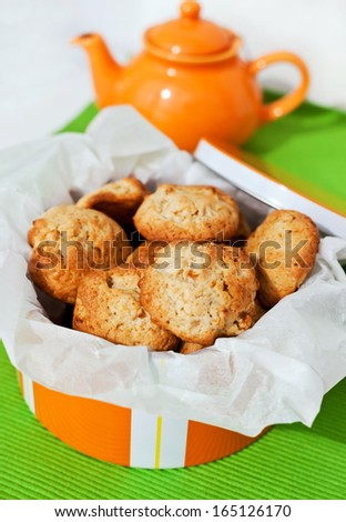 Homemade apple cookies in orange box with teapot on the background - stock photo