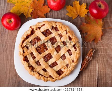 Homemade apple pie, apples and autumn leaves on the wooden table - stock photo