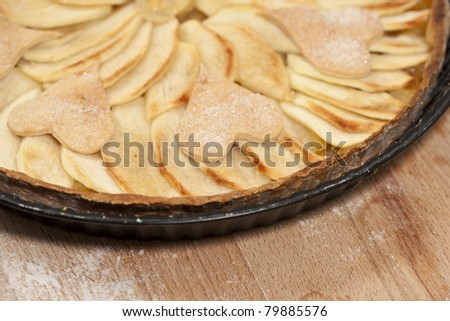 Homemade apple pie decorated with hearts.