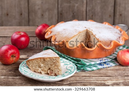 Homemade apple pie in an orange ceramic form on old wooden table. Selective focus and rustic style. - stock photo