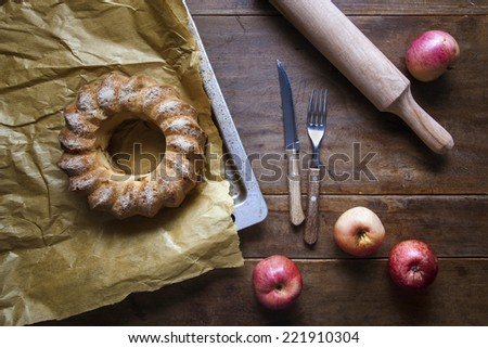 homemade apple pie on parchment paper with apples on old  dark wooden table rustic style - stock photo