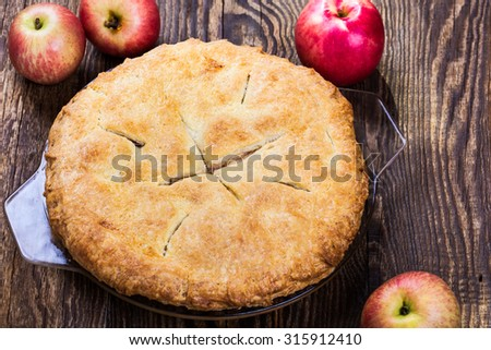 Homemade apple pie  with a flaky pie crust and sliced apples, sugar, allspice, cinnamon, vanilla on rustic wooden table - stock photo