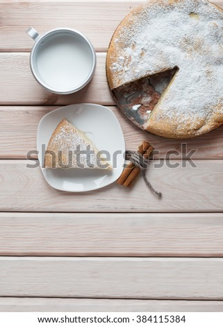 Homemade apple pie with cinnamon sticks on a wooden table. A piece of apple pie and cup of milk. Top view. - stock photo