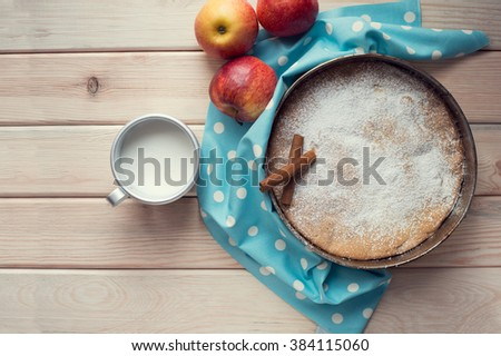Homemade apple pie with red apples and cinnamon sticks on a wooden table. A piece of apple pie and cup of milk. Top view. - stock photo