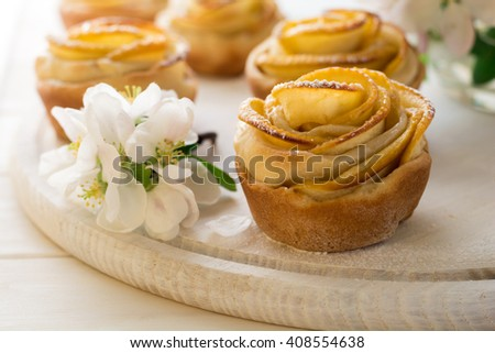 Homemade apple rose cakes decorated apple blossom on white wooden desk - stock photo