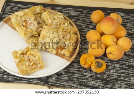 Homemade apricot cake on a plate. Freshly picked apricots on a wooden table. Homemade dessert of summer fruits. - stock photo
