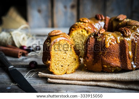 Homemade autumn cake with nuts and caramel on wooden background - stock photo