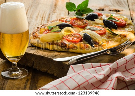 Homemade bacon pizza with tomatos onion olive basil and a glas of beer on a wood plate - stock photo