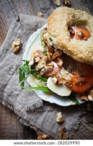 Homemade bagel filled with goat cheese and tomato - stock photo