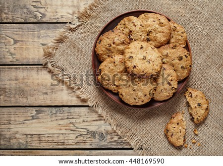 Homemade baked cereal oatmeal cookies with raisins and chocolate healthy sweet dessert snack food on vintage cloth on wooden table background. - stock photo