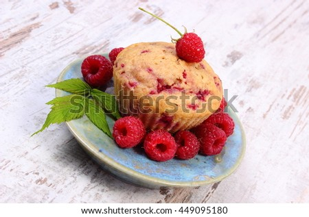 Homemade baked cupcake with raspberries and fresh fruits on plate, old rustic wooden background, delicious dessert - stock photo