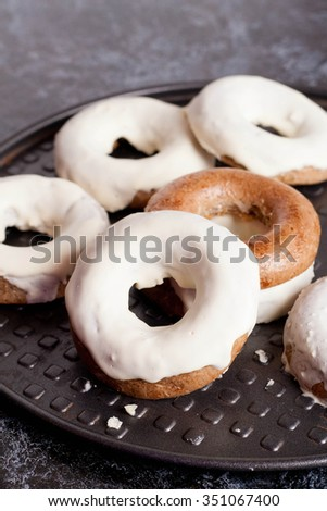 homemade baked donuts with white glaze, close up, vertical - stock photo