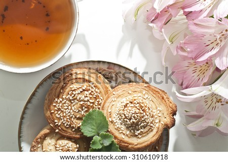 Homemade bakery, puff cookies with sesame seeds on plate, english tea and tender beautiful flowers - stock photo