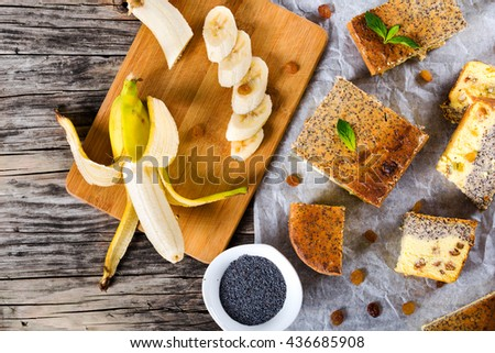 homemade banana cheesecake with poppy seeds and raisins on a parchment paper on an old wooden table with pieces of on a cutting board, in a small bowl, close-up