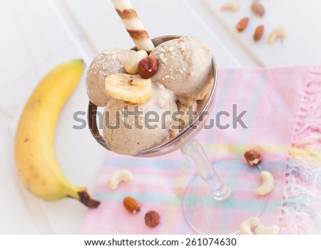 Homemade banana ice cream decorated crushed nuts - stock photo