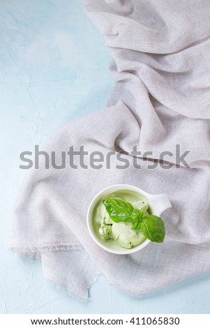 Homemade basil ice cream with fresh basil leaves in white ceramic bowl on white textile rag over blue textured background. Top view