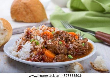 Homemade beef and vegetable casserole served with rice on white plate, comfort food for a cold day