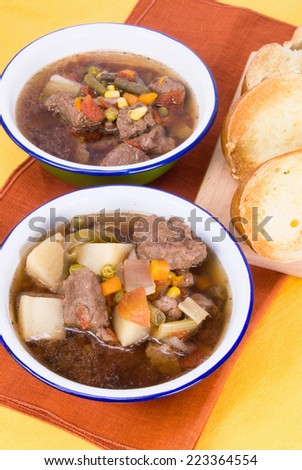 Homemade beef soup served with buttered toasted crusty italian bread. Soup ingredients are potatoes, mixed vegetables, low sodium beef broth, onions, celery. Shallow definition of field.  - stock photo