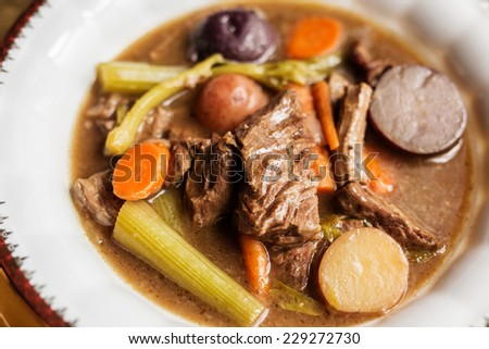 Homemade beef stew in a white porcelain gold rimmed bowl on a wooden table.  - stock photo
