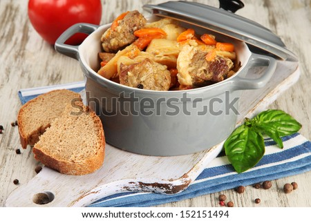 Homemade beef stir fry with vegetables in color pan, on wooden background