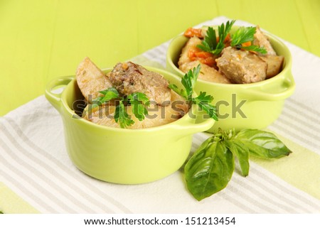 Homemade beef stir fry with vegetables in color pans, on bright background