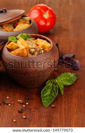 Homemade beef stir fry with vegetables in pots on wooden background