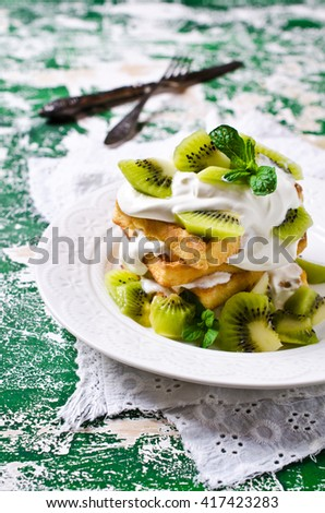 Homemade Belgian waffles with cream and kiwi. Selective focus.