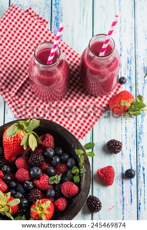 Homemade berries smoothie in vintage milk bottles - stock photo