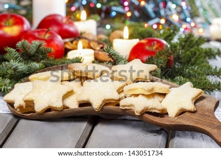 Homemade biscuits in star shape on wooden table in christmas eve setting - stock photo