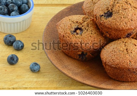 Homemade blueberry bran muffins on rustic wooden plate with blueberries in horizontal format  and shot in natural light