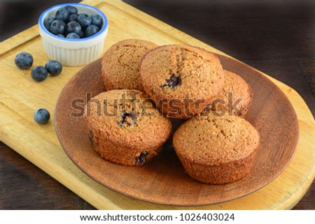 Homemade blueberry bran muffins with fresh blueberries on rustic wooden background in horizontal format and shot in natural light